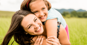 Comprehensive Dentistry - A little girl hugging her mom in a grassy field both have beautiful smiles.
