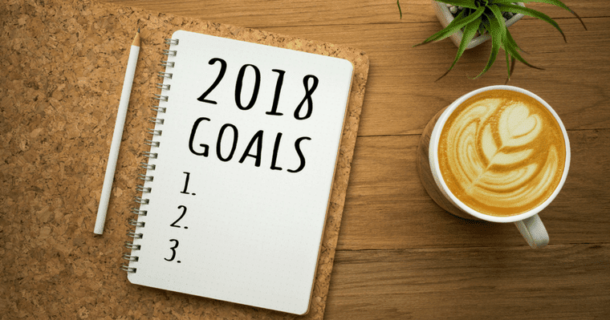 "A pencil next to a notebook with the words ""2018 Goals""."